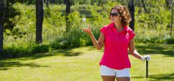 Woman tossing golf ball in the air at a golf course.